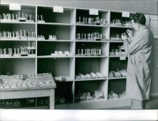 Year ? Man standing in front of shelf in the shop testing, checking and experimenting something in a small bottles.