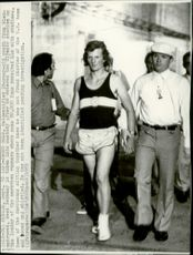 Unidentified young man is taken away after unlawfully sprung into the ranks of the marathon runners during the 1972 Olympic Games