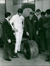 Men looking at tyre of a Renault Alpine curiously.