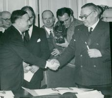 Bevin and Bidault congratulate each other after signing the 50-year English-French Alliance Treaty