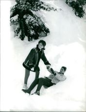 Sacha Distel and his wife Francine Bréaud having fun in the snowy field.  Taken - Jan. 1963
