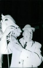 Fernandel striking a pose while holding a horse face, 1971.