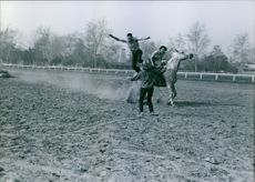 Buzz Henry with Patty Foley, Buzz's fiancee, piloting the horse, Buzz is making a dramatic leap at Marta Kristen.