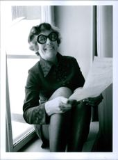Marianne Nielsen smiles at the photographer while she reads the letter. 1970.