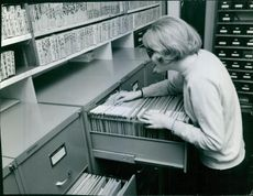Woman opening the locker and looking the files.