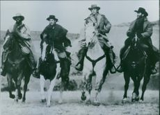 A photo of actors Kevin Kline, Scott Glenn, Kevin Costner and Danny Glover in a film Silverado shown 1985.
