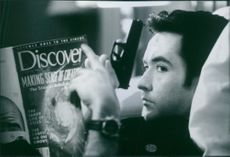 """A photo of John Cusack as Martin Q. Blank holding a gun in the film """"Grosse Pointe Blank"""". 1997."""