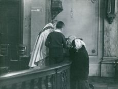A man and a woman receiving communion by a priest in the Church.