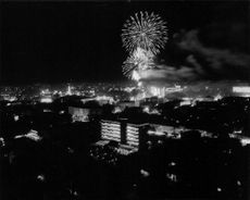 An aerial night view of Paris with fireworks.