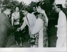 Men The Lao Royal Family shaking hands.
