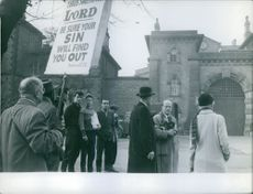 A man holding a placard in a gathering.