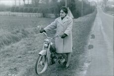 Woman with motorcycle standing on the roadside in the village.