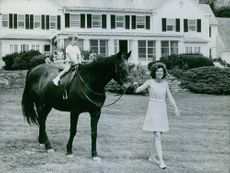 Eunice Kennedy Shriver with her son, while riding a horse, 1968.