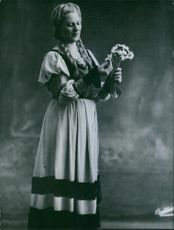 Renata Tebaldi standing with some flower.