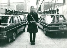 A policeman in long braids with lines of grenadiers behind him in front of parliament before opening the Riksdag