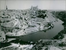 An aerial view of the inhabited city in Toledo, Spain, with the  Alcázar and Primate Cathedral of Saint Mary dominating the skyline.