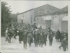 Policemen holding and taking away prisoners from the street.