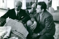 Gaston Naessens reading the newspaper with two unknown men. 1964.