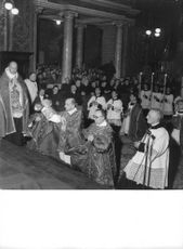 Pope Paul VI worshiping in church with other Priest, crowd stood behind of them with Devotion