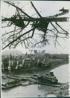 Soldiers standing while looking the tank in the bridge during Second Sino-Japanese War.
