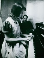 Victor Borge looking at girl, playing piano.
