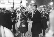 Princess Soraya standing with Prince Orsini in a busy street.