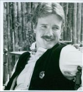 Cowboy Linden Ashby sitting on a chair in a country side.  In the film