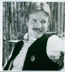 "Cowboy Linden Ashby sitting on a chair in a country side.  In the film ""Wyatt Earp"""