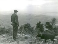 Gaston Bonheur with his dog standing on a cliff overlooking a view in distance.  - Jan 1966