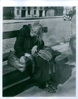 "An old woman sitting on a bench.   ""poor donated"""