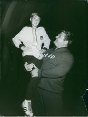 A big man carrying a boy wearing a medal. October 27, 1968.