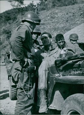 A soldier talking to a wounded man while siting in the jeep in Korea. 1950.
