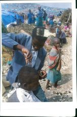 The Rwandan War:A rwandan refugees gives a haircut.