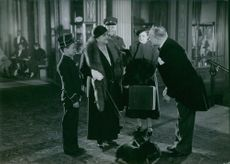 People standing together and communicating with each other.  1934 Grand Hotel