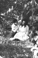 A man and a woman sitting under a tree.