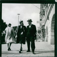Maurice Chevalier walking with a woman on sidewalk.