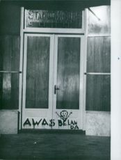 "Photo of vandalism on the door, ""Awas Belanda"""