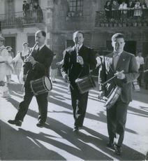 A group of men playing a drum in the road while the other people are dancing.
