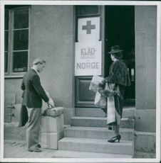 Man and woman standing in front of a building with their things during the war in Norway, 1940.