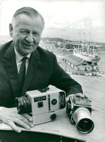 Victor Hasselblad shows the camera (t.v.) that the astronauts photographed from.