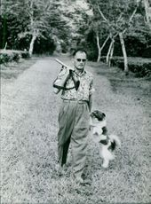 Man walking with a dog while holding a gun on his right hand in Fransk, Indokina.  Taken - 29 Jan. 1964