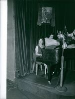 Jacqueline Boyer siting with a woman and playing piano. 1960