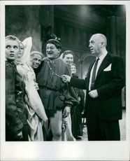 Jean Plays Hoan Film maker Otto Premingar talking to the cast of St. Joan. Jean Seberg, who plays the name part, seen left, and peeping through to enjoy the joke is Richard Widmark.