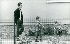 Jacques Charrier walking behind his son.