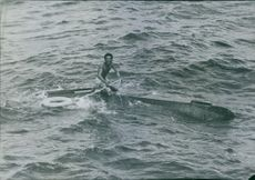 A man floating on a debris in the sea.