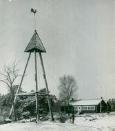 The bell tower at Hammarbystugan in Nacka open-air reserve with Hammarby cottage in the background