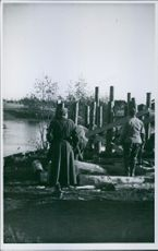 Workers standing and working beside the river.