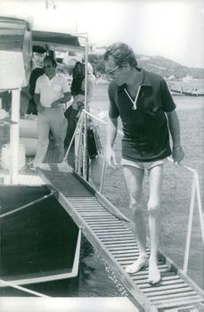 Antony Armstrong-Jones, 1st Earl of Snowdon smiling and looking down while on a dock.