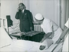 Prince Alexander of Yugoslavia talking on the phone while looking at the nurse wrapping his child with a blanket. 1959.