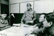 Army team leader in discussion with his comrades in Vietnam.